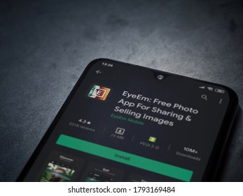 Lod, Israel - July 8, 2020: EyeEm - Sharing and Selling Images app play store page on the display of a black mobile smartphone on a dark marble stone background. Top view flat lay with copy space.