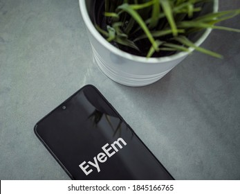 Lod, Israel - July 8, 2020: Modern minimalist office workspace with black mobile smartphone with EyeEm app launch screen with logo on a marble background. Close up top view flat lay.