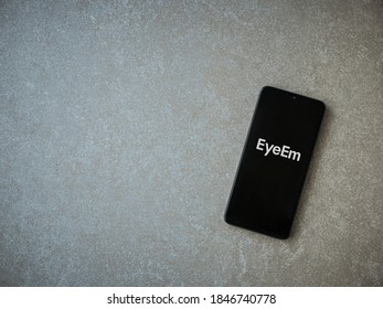 Lod, Israel - July 8, 2020: EyeEm - Sharing and Selling Images app launch screen with logo on the display of a black mobile smartphone on ceramic stone background. Top view flat lay with copy space.