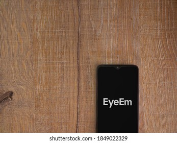 Lod, Israel - July 8, 2020: EyeEm - Sharing and Selling Images app launch screen with logo on the display of a black mobile smartphone on wooden background. Top view flat lay with copy space.