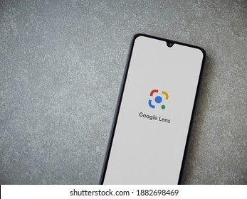 Lod, Israel - July 8, 2020: Google Lens app launch screen with logo on the display of a black mobile smartphone on ceramic stone background. Top view flat lay with copy space.