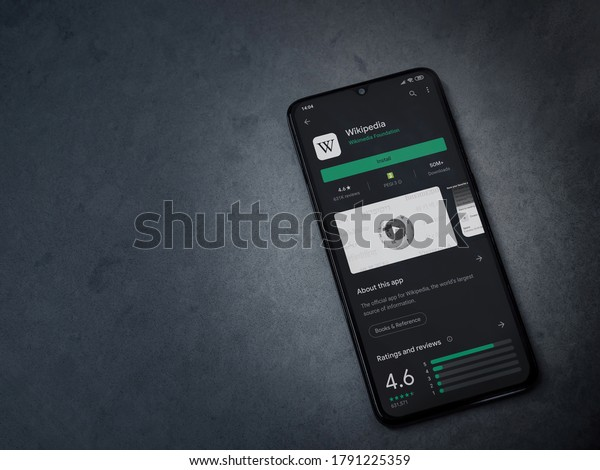 Lod, Israel - July 8, 2020: Wikipedia app play store page on the display of a black mobile smartphone on a dark marble stone background. Top view flat lay with copy space.