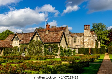 Lode, Cambridgeshire /  UK - MAY 11 2019: old building on the park with red roof, sky is blue and white and grey clouds above the building