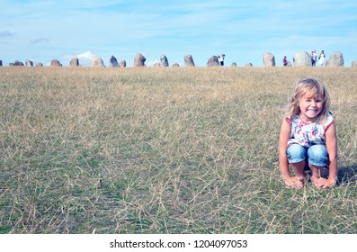 Loderup, Sweden - August 04 2010: The stones of Ale (Ales Stenar) is the swedish answer for Stongehenge. Here shown in the background in Kaseberga in the South. Little girl is visiting during Summer.