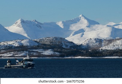 LODINGEN, NORDLAND COUNTY / NORWAY - MARCH 01 2020: Winter view on the mountains of the island of Hinnoya (Hinnøya). Fishery vessel near Lofoten Islands