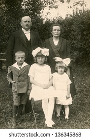 LODZ, POLAND, CIRCA 1930 - Vintage photo of unidentified parents with three children in garden, Lodz, Poland, circa 1930