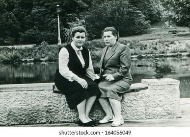 LODZ, POLAND, CIRCA FIFTIES: vintage photo of two women sitting on wall, Lodz, Poland, circa fifties