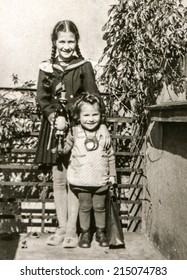 LODZ, POLAND, CIRCA FIFTIES: Vintage photo of two little girls on balcony