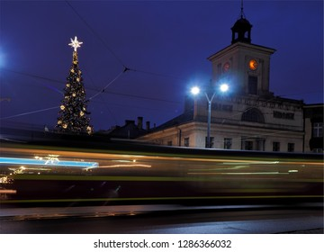 Lodz, Poland - December 28, 2018 Blurred motion of the city tram against the background of the town hall and the decorated Christmas tree in Lodz.