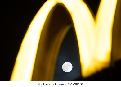 Lodz, Poland, January 1, 2018 yellow McDonald's sign, night, clouds, moon in background, McDonald's was founded in 1940 as restaurant operated by Richard and Maurice McDonald, in San Bernardino, USA