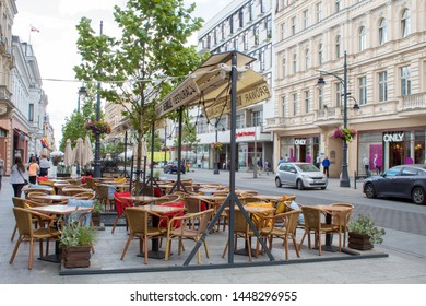 Lodz, Poland - July 09 2019: Cozy cafes with tables and tables for tourists in the central historical street of the Polish city of Lodz at the height of summer.