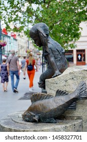 LODZ, POLAND JULY 19 , 2019:Drinking fountain decorated by sculptures of kids and a catfish on central Piotrkowska Street in Lodz, Poland