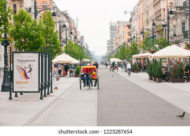 Lodz, Poland, July 2018. Famous Piotrkowska street in the heart of Lodz city. People on Cycle rickshaw