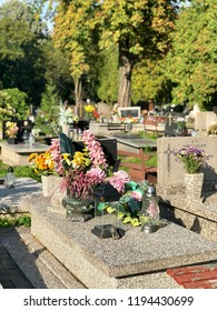LODZ, POLAND- September 17, 2018: A gravestone with flowers and candles on a cemetery.