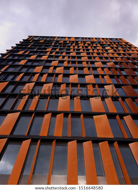 """LODZ, POLAND - SEPTEMBER 20, 2019: Facade of the """"City Gate"""" office building in Lodz city center, Poland. View from below."""