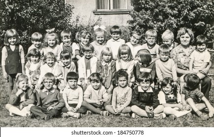 LODZ,POLAND, CIRCA 1960's: Vintage photo of group of little classmates and teacher posing together outside in front of the school