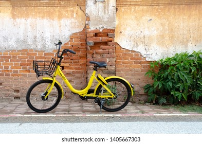 Loei, Thailand - 26 February 2018: Ofo bike parked by the wall of Ofo is a bicycle sharing service provider.
