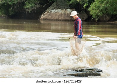 LOEI ,Thailand , 8 AUG 2018 : The man catching fish at the waterfall