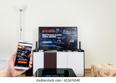 LOEI, THAILAND - APR 1, 2017: Man holds a white smart phone that shows movies from Netflix. Netflix is an entertainment company, specializes in and provides streaming media and video on demand online.