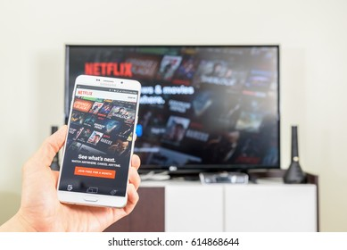 LOEI, THAILAND - APR 4, 2017: Man holds a white smart phone that shows movies from Netflix. Netflix is an entertainment company, specializes in and provides streaming media and video on demand online.