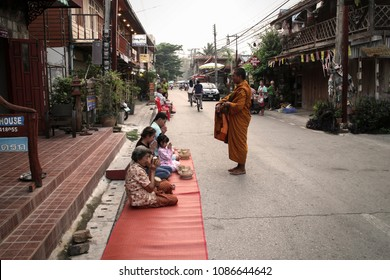 Loei, Thailand - April 13, 2016: People give alms to a Buddhist monk at Chiang Khan Street Loei Thailand.