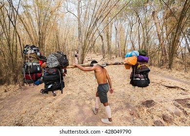 Loei, Thailand - February 14, 2014: Sherpas are carrying a lot of baggage of tourists on his shoulder and go up to the top of mountains in Phu Kradueng National Park.