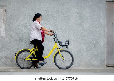 Loei, Thailand - February 26, 2018: An elderly Asian woman on a bicycle ofo is a bicycle sharing service provider.