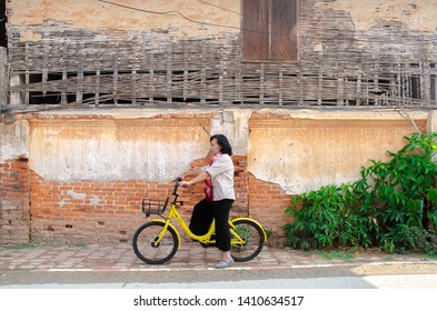 Loei, Thailand - February 26, 2018: An elderly Asian woman on a bicycle ofo is a bicycle sharing service provider.Do not focus on the main object of this image.