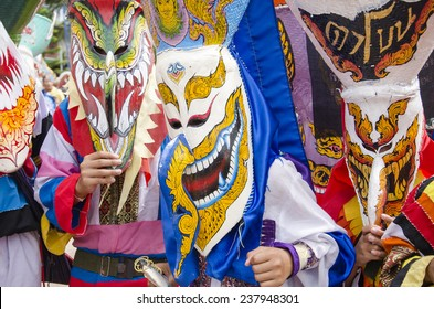"""Loei, Thailand - June 23, 2012 : People are dressing with colorful clothes and put the hand made mask which made from wood or threshing bamboo in ghost mask festival or """"Pi Ta Khon"""""""