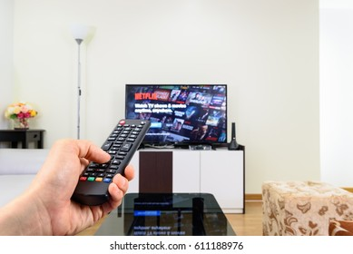 LOEI, THAILAND - MAR 30, 2017: Man holds a remote control and selects a movie from Netflix. Netflix is an entertainment company, specializes in and provides streaming media and video on demand online.