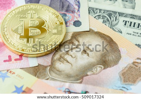 LOEI, THAILAND - NOV 3, 2016: Gold Bitcoin on banknotes i.e. Chinese RMB CNY yuan. Bitcoin is a digital / virtual / cryptocurrency and a payment system invented by an unidentified Japanese programmer.