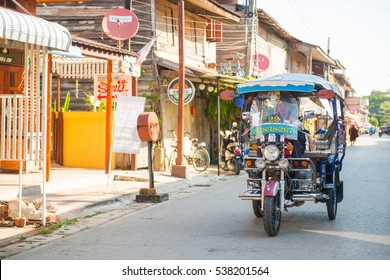 Loei, Thailand - November 26, 2016 :The old wooden houses in walking street market of Chiang Khan at Loei, Thailand, Tuk Tuk (Taxi)