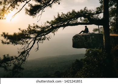LOEI, THAILAND-December 26, 2018 : Unidentified man sit on the edge cliff to see the sunset at Lom Sak cliff, Phu Kra Dueng national park, Loei, Thailand.