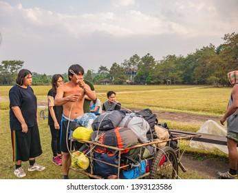 Loei/Thailand-16 Feb 2019:Unacquainted porter man waiting trekkers to pick them Bag on Phu Kradueng mountain national park in Loei City Thailand.