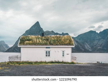 Lofoten Islands Norway - September 2018: House with traditional grass roof and mountains in the background on a cloudy day. Lofoten is an archipelago and a traditional district in the county of