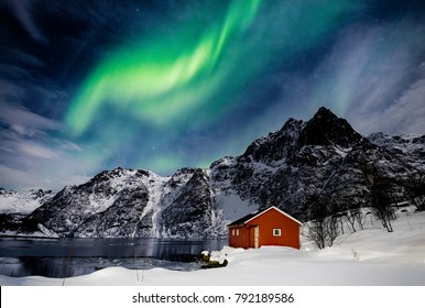 Lofoten Islands, Svolvaer, Northern Lights over a frozen lake and red rorbu, Norway.