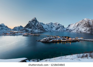 Lofoten mountain landscape with Sakrisoy island, Norway with illuminated fisherman's cabins during evening twilight in calm water. Winter  panorama with snow-covered mountains.