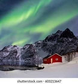 Lofoten, Svoelver, Aurora Borealis over a frozen lake and red rorbu, Norway.