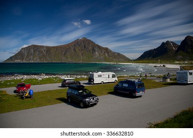 LOFOTEN,NORWAY - JUNI 25: Overlooking a fine sandy beach with camping and high mountains in the horizon Lofoten,Norway,Juni 25,2015