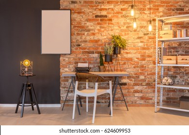 Loft apartment with brick wall, desk, chair, chalkboard, lamp, plants
