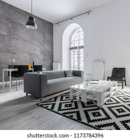 Loft apartment with gray sofa, pallet table, carpet and studio lamp