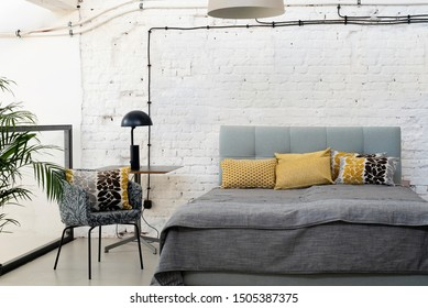 Loft apartment with white bricky wall and double grey bed. Interior in scandinavian style with copy space on the wall.