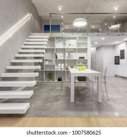 Loft apartment with white mezzanine staircase, table, chairs and open kitchen