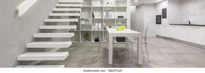 Loft apartment with white staircase, table, chairs and open kitchen, panorama