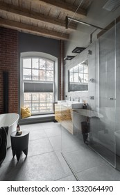 Loft bathroom with big window, wooden ceiling and brick wall