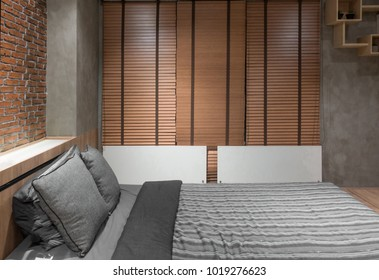 loft bedroom with bed near brick wall and wooden curtain