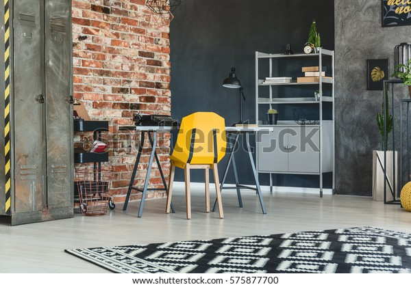 Loft interior with brick wall, desk, yellow chair and bookcase