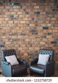 Loft interior concept. Two leather sofa and pillows on Brick wall background with copy space vertical style.