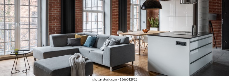 Loft interior with corner sofa and kitchen island, panorama