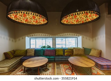 Loft interior design, comfortable sofa with pillows, colored mats, round table